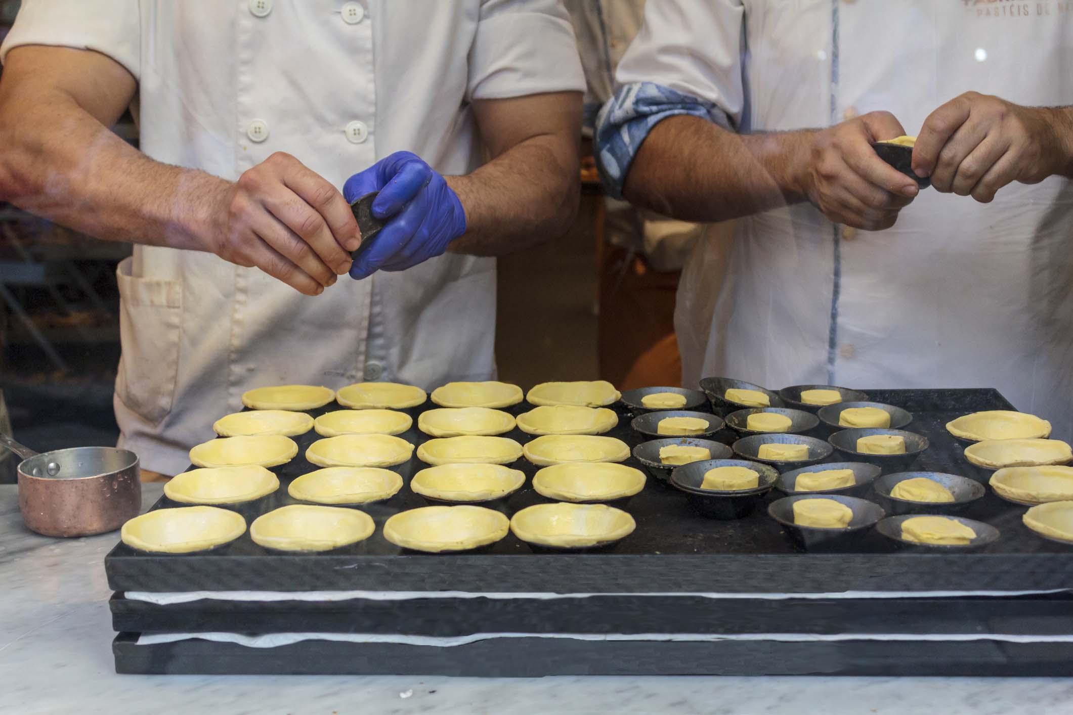 "Confectioners making dough for the famous Portuguese cake ""Pastel de Nata"""